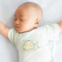 baby sleeping on back with arms spread