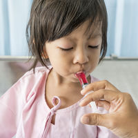 child getting medicine with syringe