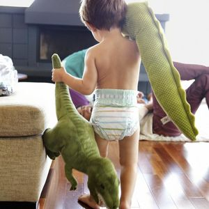 Little Boy Running In Diapers Holding Green Dinosaurs