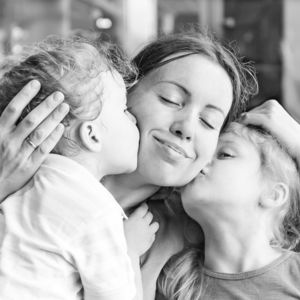daughters kissing mom on cheeks