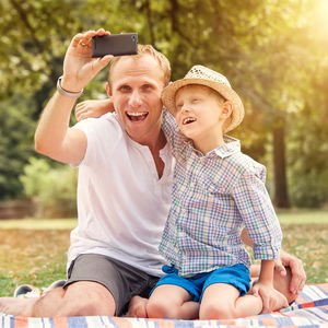 dad and son taking selfie on smartphone