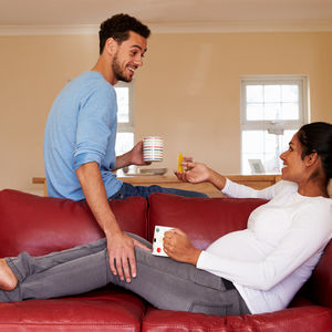 pregnant woman drinking coffee on the couch