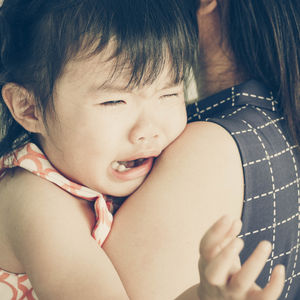 little asian girl crying on mom's shoulder