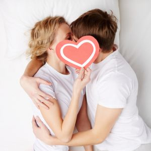 young couple kissing in bed