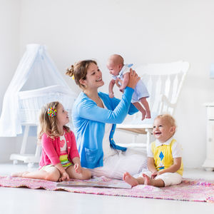 Mother Playing With Children Inside Pink Yellow Blue Cardigan