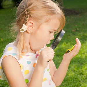 girl looking at bug with magnifying glass