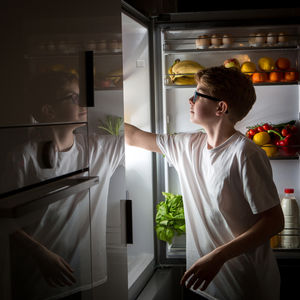 boy looking for midnight snack in the fridge