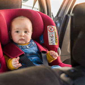 baby in rear facing car seat, red