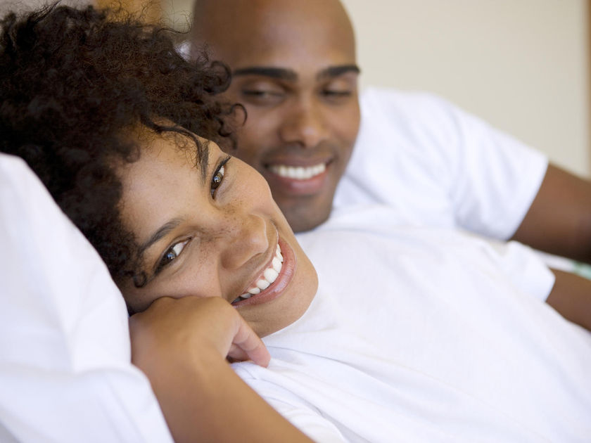 Young couple smiling in bed
