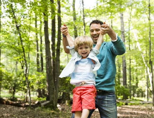 Raise Optimist Dad Lifts Son in Red Shorts Playing Outside Forest
