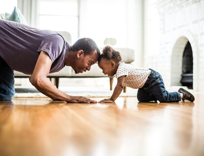 Father and toddler daughter playing on the floor