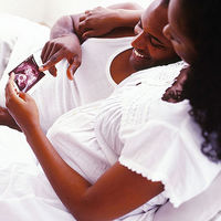 pregnant couple looking at ultrasound picture