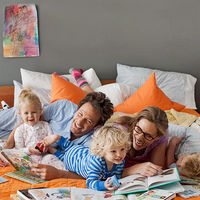 family in bed reading