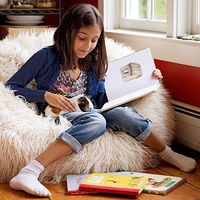 child reading with pet guinea pig