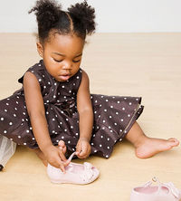 toddler learning to put on shoes