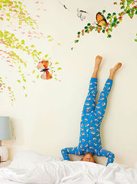 Child Standing on Head in Bed