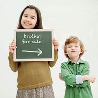 "Girl holding ""brother for sale"" sign"