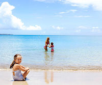 Girl on beach and girl and woman in ocean