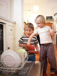 Two boys putting dishes in the dishwasher