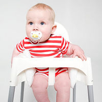 baby in highchair with pacifier