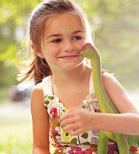 child holding dinosaur toy