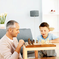 smiling dad playing chess with son