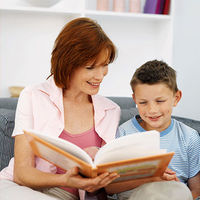 Red haired mom on couch with freckled son reading book