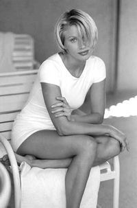 blonde woman sitting on chair in white clothes