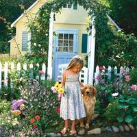 little girl with dog in front of playhouse
