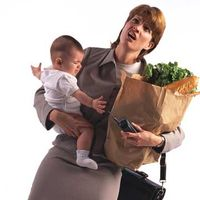 Working mother juggling baby and groceries