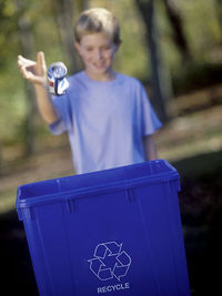 boy throwing can in recycle bin