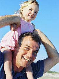 Dad with daughter on shoulder's, holding her hands