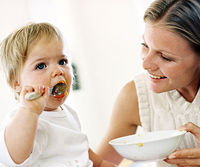 Mom helps toddler eat