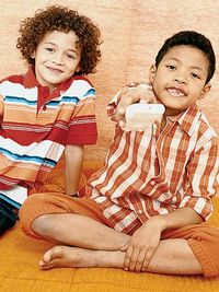 Two Boys Holding TV Remote Control