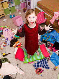 girl standing in messy room