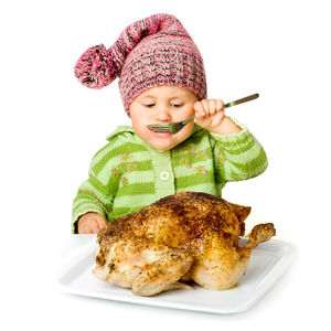 child in hat eating chicken