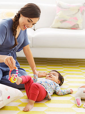 Baby laying on rug plays with toy using feet