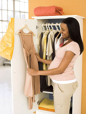 pregnant woman looking through her closet