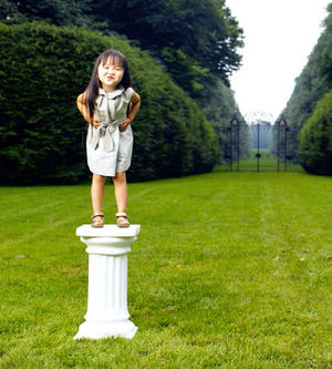 little girl standing on a pedestal