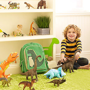child playing with toy dinosaurs