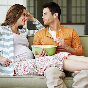 happy pregnant couple enjoying popcorn