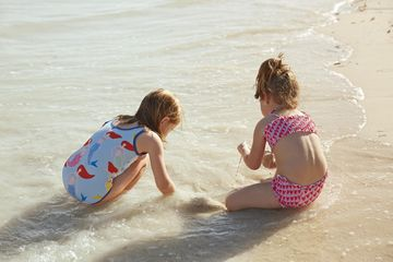 Two Girls Playing in Sand on Beach
