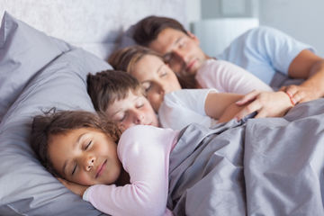 Cute family sleeping together in bed