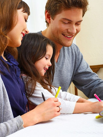 young couple with their daughter coloring