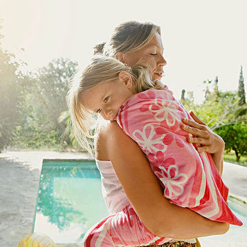 Mother holding daughter by pool