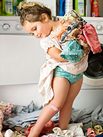 child standing in pile of clothes