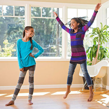 Two girls in sunny room, one doing jumping jacks