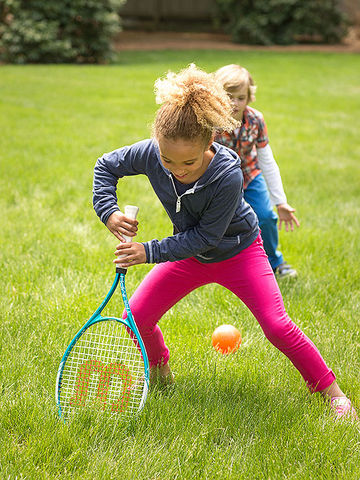 French Cricket: girl looking down at racket and ball