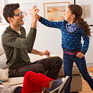 Girl and dad high-fiving