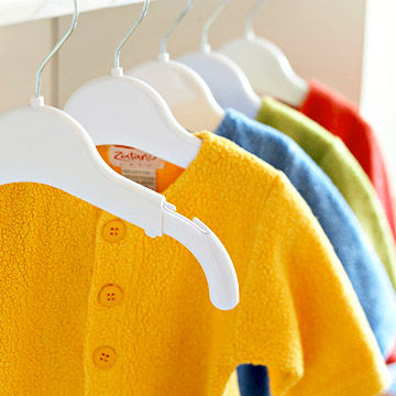 bright sweaters on expandable hangers in Ultimate Nursery closet